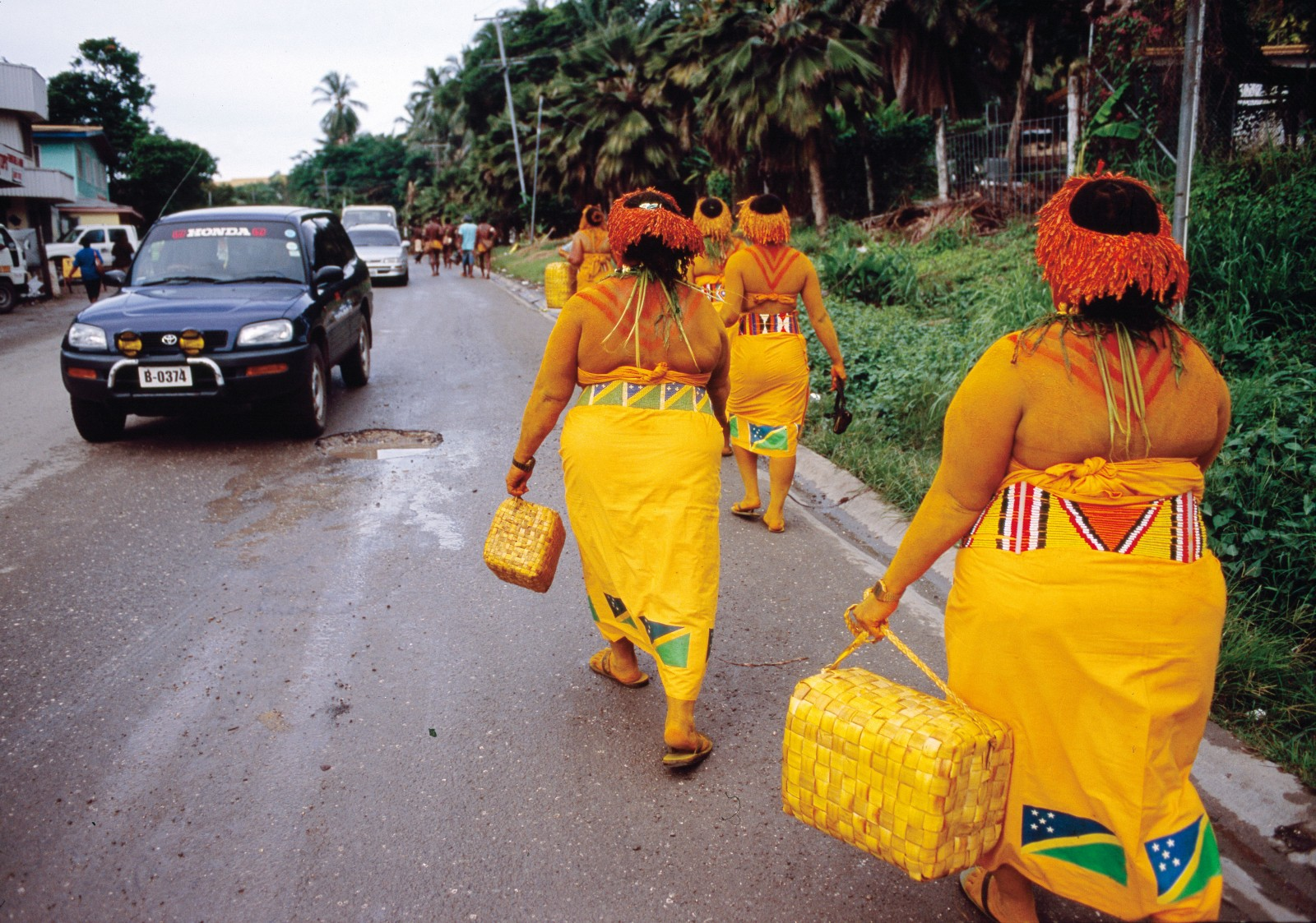The women of Ontong Java atoll hasten to the closing ceremony of the festival. The atoll is part of the Melanesian Solomon Islands but considered Polynesian by culture. However, their troupe, pictured here with pungent turmeric smeared onto costumes and limbs, performs with vocals and dance forms that contrast with those of both Pacific regions. How such enormous cultural and linguistic diversity can exist, despite relatively frequent contact with other islands, remains the focus of research by the many anthropologists and historians interested in the Pacific region.