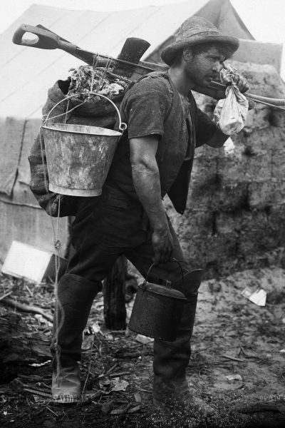"A fully kitted-out gumdigger with spear, spade and axe on his shoulder, a bucket for sluicing, a billy for the midday brew and a haversack or ""pikau"" for carrying the day's haul. The small flour bag in the digger's hand was kept handy, usually attached to the belt, for storing small pieces of gum encountered while digging for larger specimens."
