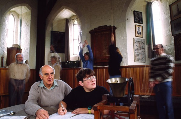 One of Christchurch Cathedral's up-and-coming ringers, John Clayton (age 15), watches the changes intently while referring to a manual of ringing methods. Bob Bennett supervises.
