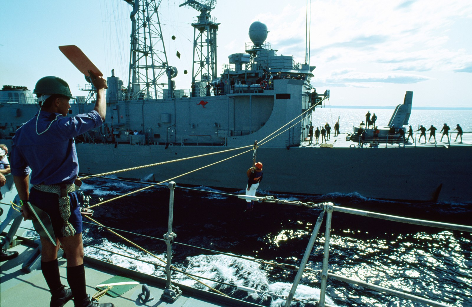 """Batman"" Able Seaman ""Bungy"" Williams uses a system of bat signals to control a manoeuvre known as a ""jackstay,"" in which stores, ammunition or personnel are transferred from one ship to another while at sea. These evolutions take place in all weathers, not just in calm conditions as is the case here with HMAS Adelaide, an Australian Guided Missile Frigate, and require precise stationkeeping and good communications. Although telephone contact is established between ships, bats are used in case the telephone lines part or break in heavy seas."