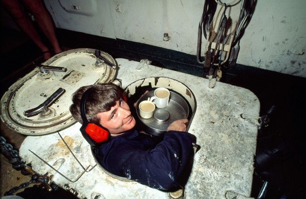 """When you go full speed [28 knots] you have to keep a goad eye on the instruments or she blows up!"" say Southland's engineers (""steamies,"" in navy parlance). The boiler room has a plaque on the hatchway which reads ""Welcome to thermal wonderland."" It's not far of! the truth: the air temperature here can reach 700 e as the frigate'S two controlled superheat boilers supply steam for the two sets of turbines that drive the screws, developing 30,000 shaft horsepower. Below: tea time in ""geyserland."""