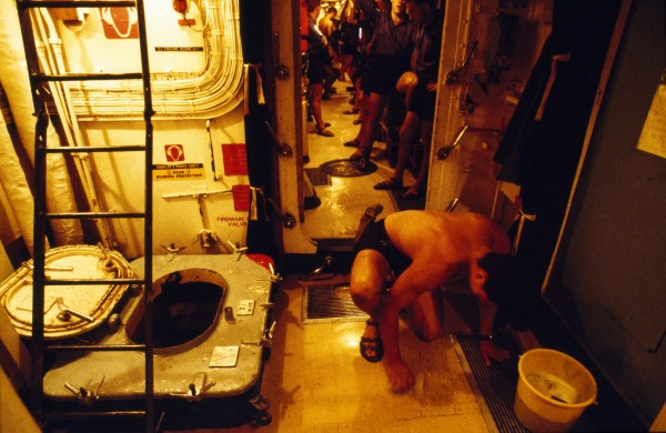 """""""Join the Navy and see the deck,"""" quips a junior rating in between scrubs. Vinyl is cleaned in two halves, port and starboard, to allow passage for the endless succession of legs which travel the ship's corridor."""