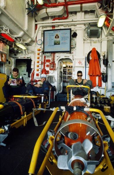 "War means waiting. In the helicopter hangar navy and air force personnel while away the hours on standby. Both anti-submarine torpedoes (orange) and depth charges (black) are dropped by the ""helo."""