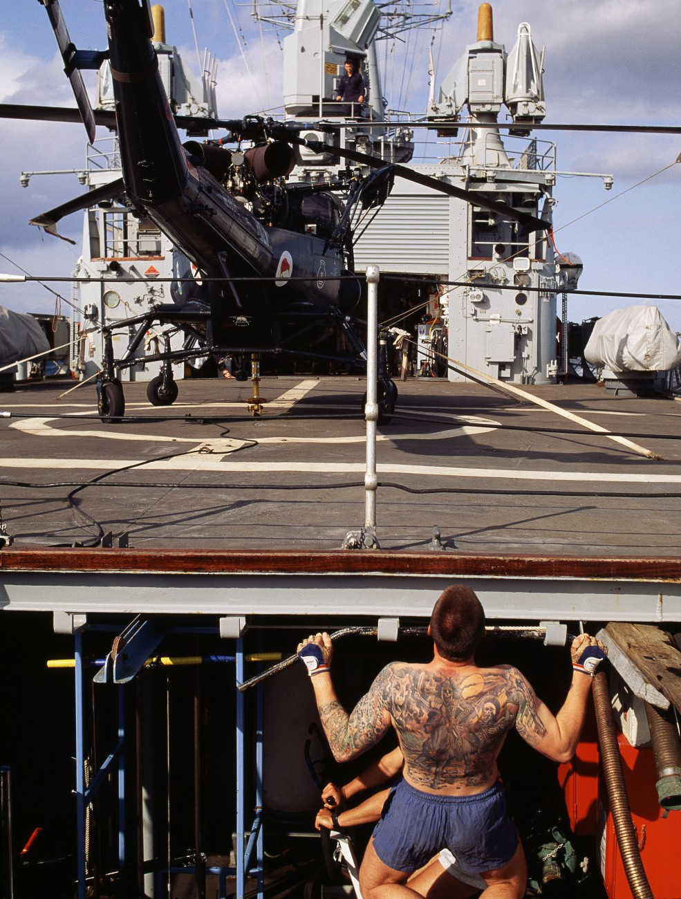 Tattoos are a part of naval traditions, and those desirous of this form of decoration soon learn in which port cities the best tattooists live. More ambitious artworks are usually outlined during the first appointment, then coloured in over succeeding months or even years as the sailor's finances and the ship's itinerary permit. Leading Seaman Jim Wilson has one of the most elaborately ornamented backs in the navy.