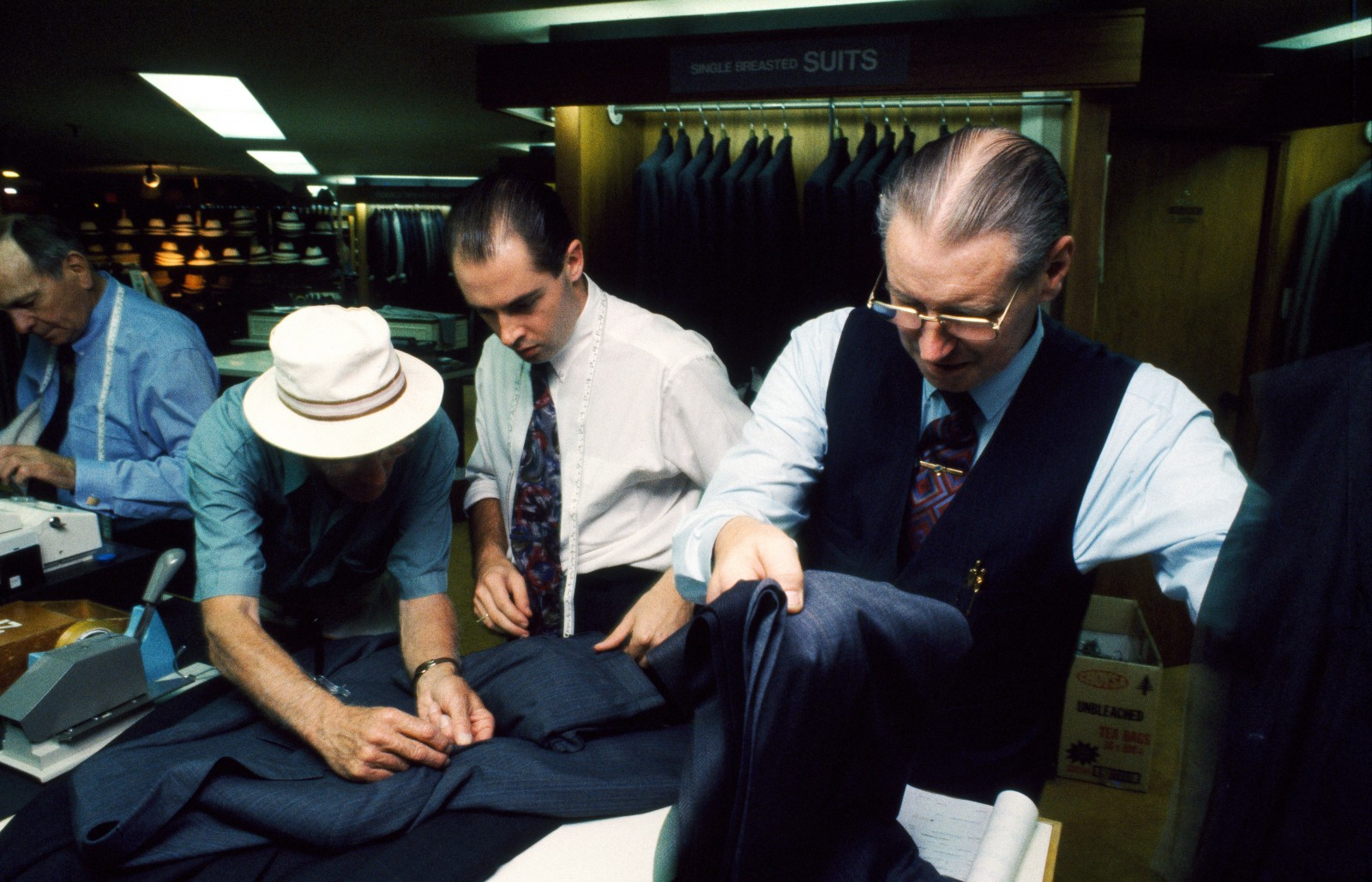 "Smith & Caughey menswear specialists Joe Chapman (far right) and John Hoskins (left) have both been selling to Queen Street patrons for most of their working lives-66 years' service between them. ""When I started, all the shirts were white,"" Hoskins recalls. The store, a Iandmark in the street, carefully maintains its tradition of old world service. Nevertheless, the famous elegance of its window displays has adapted aggressively to the '90s."