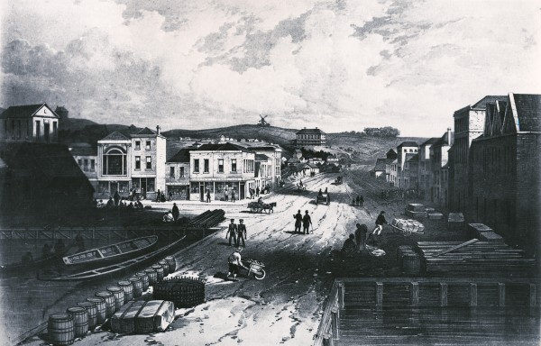 Queen Street in the 1850s was a dirt road leading inland from the all-important Queen's Wharf: the entry point to Auckland. (At this time, the water came up as far as Shortland Street.) On Karangahape Road ridge, overlooking the city, stood Partington's wind-powered flour mill, which ground the city's grain for over a hundred years before it was demolished in 1950.