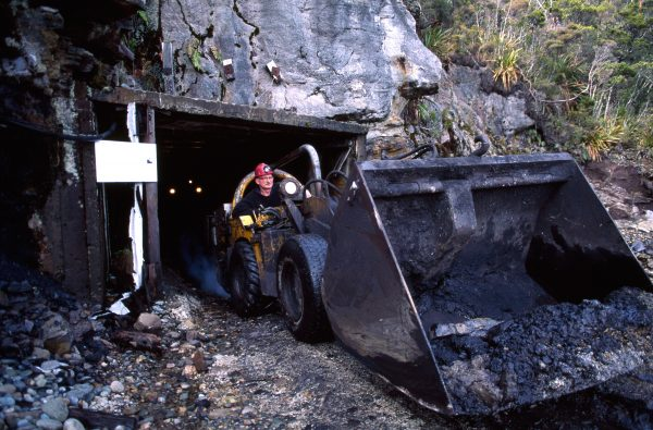 "Transporters can be a tight fit in the mine shaft. A driver was killed a few years ago misjudging the height of the roof as he rose in his seat. Engines on mine equipment are sealed to prevent ignition of explosive gases, and exhaust fumes are detoxified and passed through water ""scrubbers"" before release. Lilliputian figures put a scale to giant steps in the Island Block opencast mine in Reefton. Only the deepest of the numerous seams of coal visible is considered worth mining."