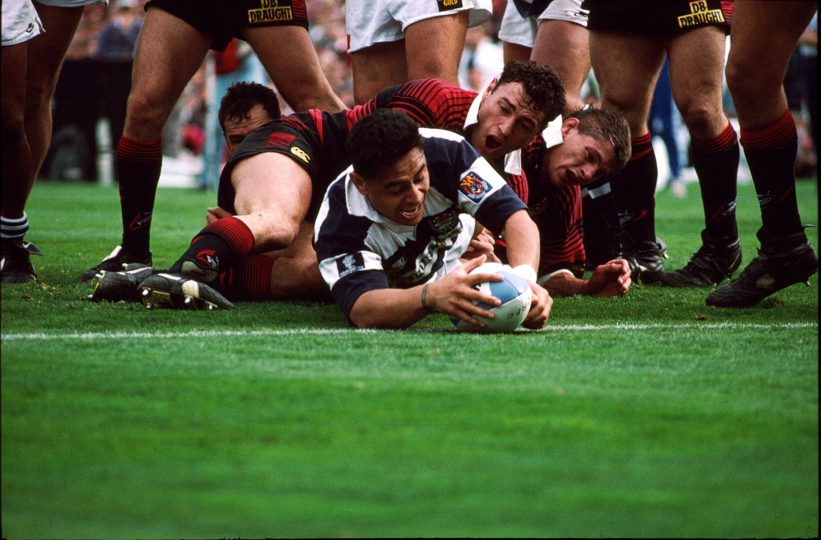 Satisfaction lights up the face of Auckland's Eroni Clarke as he grounds the ball across the try line despite Canterbury's despairing efforts to bury him during a successful Ranfurly Shielf challenge by Auckland at Lancaster Park, 1995.