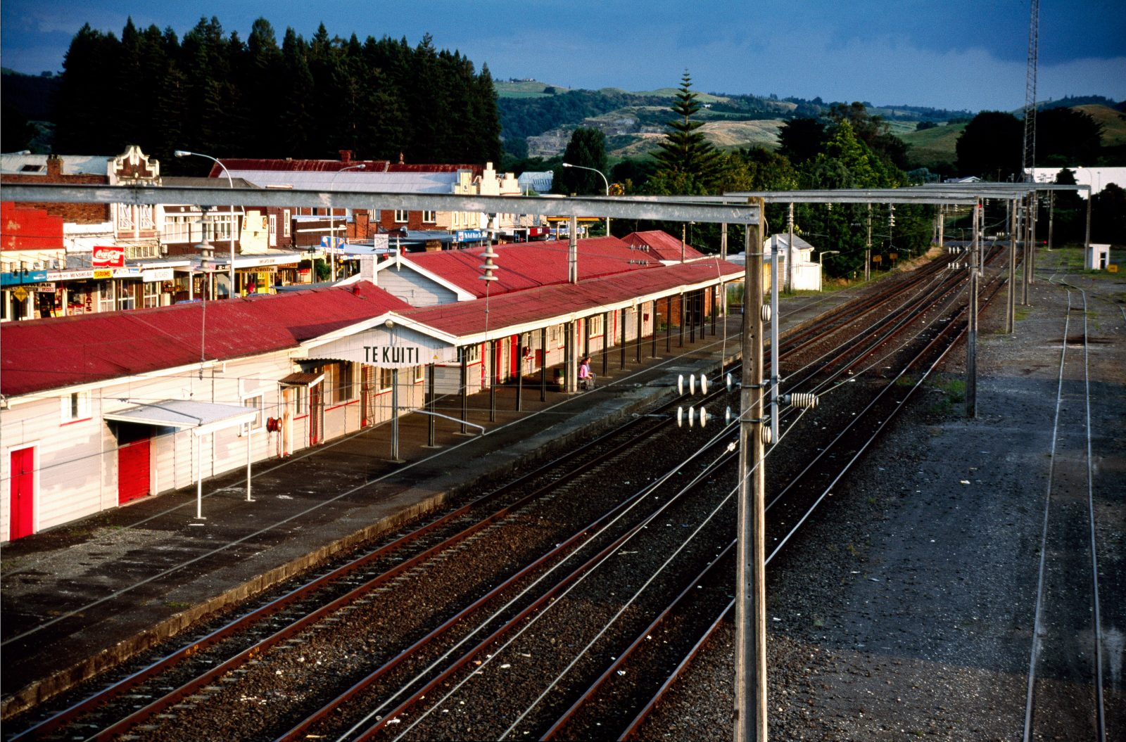 Bastion of the King Country. shearing capital of the world. Te Kuiti, like many North Island towns, grew up around the railway. The station was built in 1908—the year the Main Trunk opened—and stands as a classic of its kind, even down to the the bent rails used as verandah posts. Gantries bearing high voltage AC wires for the recent Main Trunk electrification now clutter a sky once filled with the snort and smoke of steam locomotives.