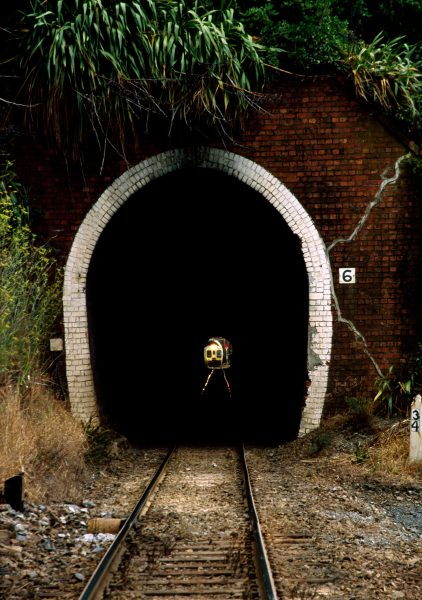 The light at the end of this tunnel is an approaching Wellington commuter train using the southern end of the Main Trunk Line. Several of these old tunnels on the outskirts of the city are too small to accommodate large railfreight containers, which have to be trucked around them.