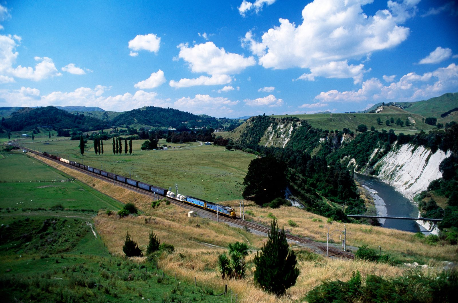 A pair of DX diesel electrics, for the last 20 years the muscle in New Zealand rail's long-haul fleet, ease a freight train across the Rangitikei flats south of Mangaweka.