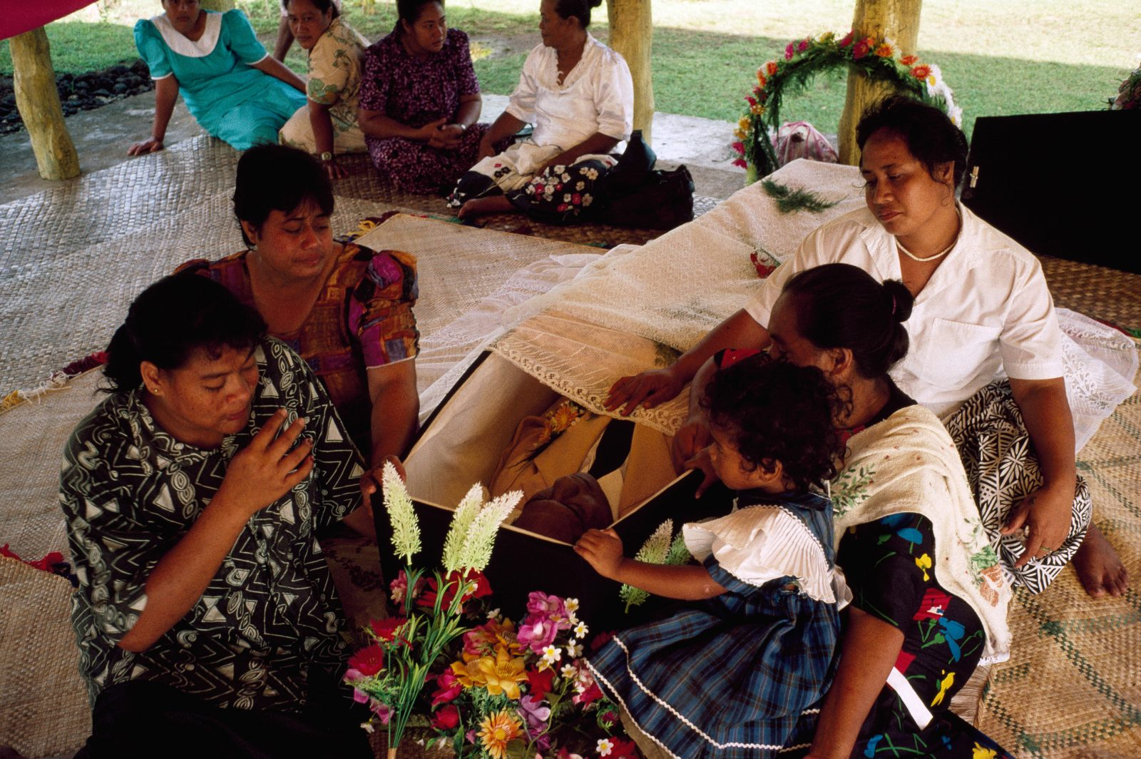 In death, as in life, the family of Elekana Tafunai of Faleasiu surround him. In Samoa, the bodies of loved ones are never left unattended, and there is no squeamishness about being near the dead person.