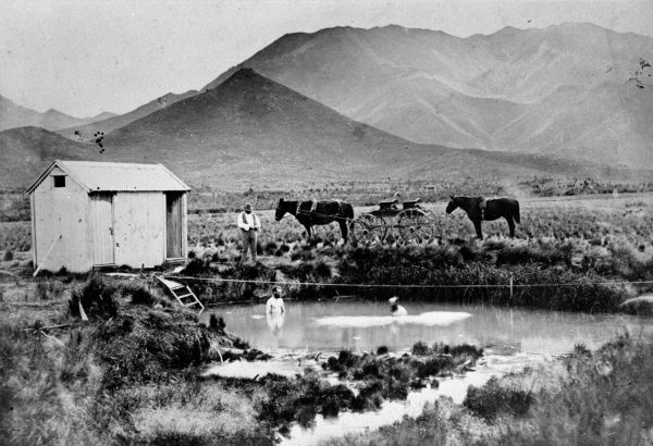 Hanmer Springs went from being a one-man-and-his-hut operation in the wilderness (pictured at right in 1878, with John Fry, the builder of the shed, on the bank) to having one of the most elegant hotels in the country, the Lodge (ca. 1950).