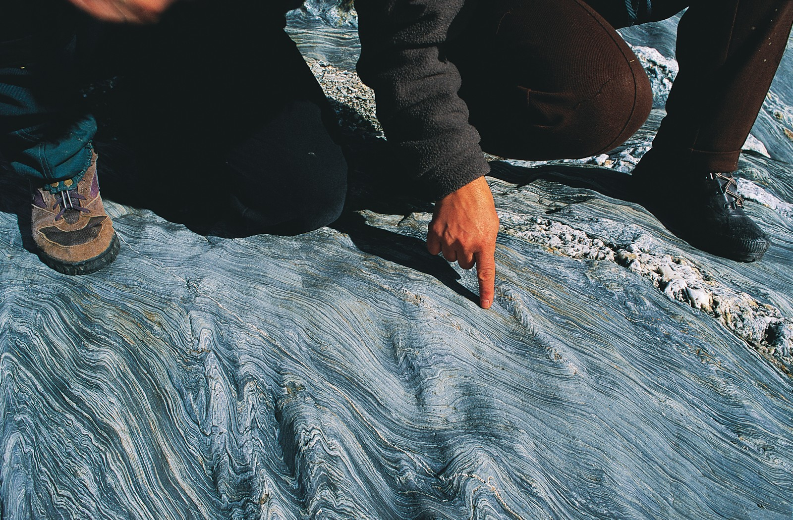 The history of the land is remembered in its rocks, and geologists can discern much from a careful examination of samples, both in the field-such as in these schists on the shore of Lake Hawea, where various cycles of deformation are discernible in the swirls-and in the lab, where samples can be dated and sections of rock examined under the microscope.