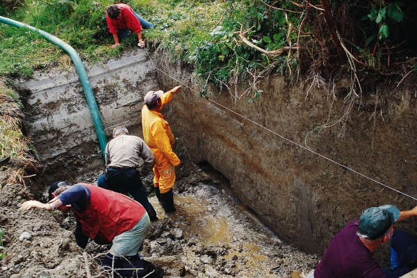 Geologists clean down the walls of a trench excavated across the Alpine Fault where it traverses river terraces near Haast. Careful analysis of the sediments and soils exposed in the wall of the trench indicated that three large earthquakes had disturbed the area in the past 900 years.