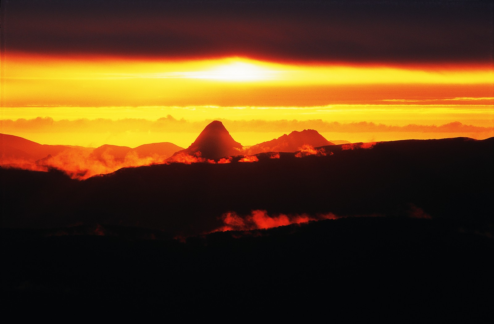 """The granity heads of Gog (at left) and Magog are silhouetted by a classic Rakiura sunset in this view to the south-west from the Tin Range. The Maori name for tis island literally means """"glowing skies."""" Golden vistas couldn't compensate for empty pockets, however, and the great tin rush of 1889 turned out to be a little more than a flash in the pan."""