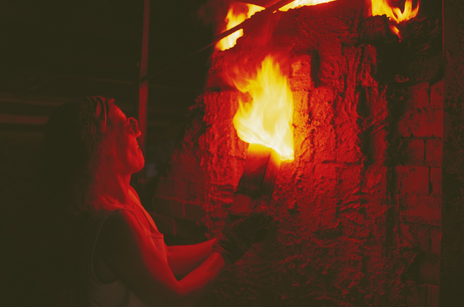 """It's like harnessing a dragon,"" says Coromandel potter Petra Meyboden, opening an observation port to check progress inside a wood-fired kiln. At its peak, the temperature will reach close to 1300°C—hotter than molten lava. Salt crystals thrown into the inferno at this point will vaporise and be carried through the kiln by the flames, creating a distinctive ""orange"" glaze on the pots and on the interior surfaces of the kiln."