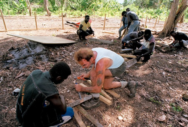 At a VSA school-building project, Kiwi volunteer Roy Bungard helps a former bush fighter with the traditional apprentice chore of building a sawhorse—the first step in learning a new trade, the first step in rebuilding a society.