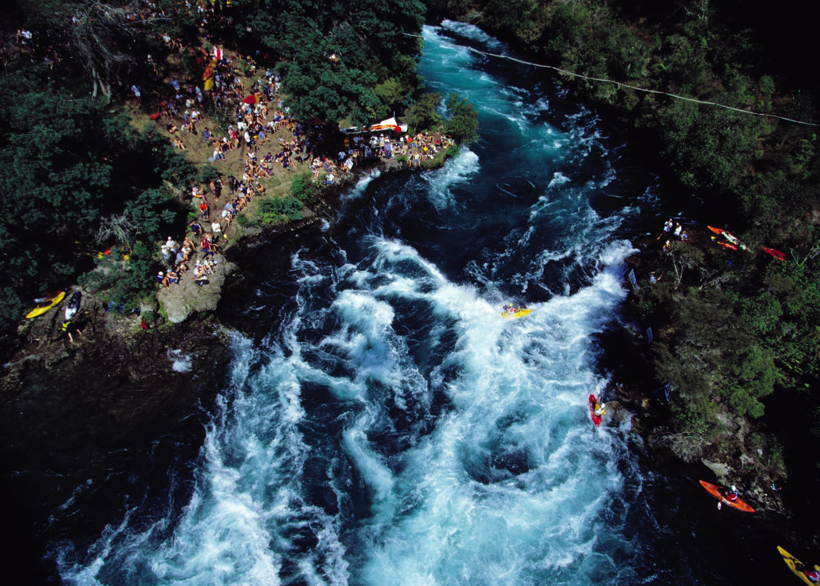 "The Fulljames Rapid, or Ngaawapurua, lies 15 km downriver of the famous Huka Falls. Here the rocky riverbed forms a permanent standing wave, the dynamics of which can be exploited by paddlers to perform an array of aquatic acrobatics. In this view, the ""holding eddy,"" where kayakers wait before sprinting out to the whitewater, can be seen to the right of the rapid. The kayakers at bottom right are sneaking around a promontory to reach the eddy."
