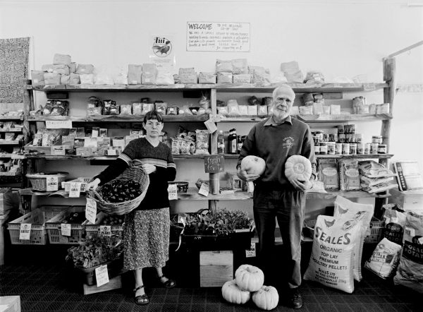 Volunteering their time, Harry Parke and Shelley Carr, restock the hand-milled kanuka and macrocarpa shelves of The Organic Coop with produce for healthy living.
