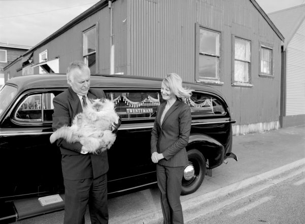 Adrian & Julie Catran, directors of Twentymans, cradle Tommie the funeral home's corpulent feline, beside the company's 1939 Chevrolet hearse, parked outside the joinery workshop where Robert Twentyman manufactured caskets from circa 1924.