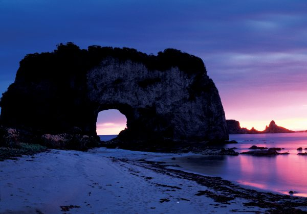 """Fiordland's Arc de Triomphe (also referred to as the """"slice of bread"""" by an earlier tramping party) is one of many rock arches that lend grandeur to the wild south coast."""