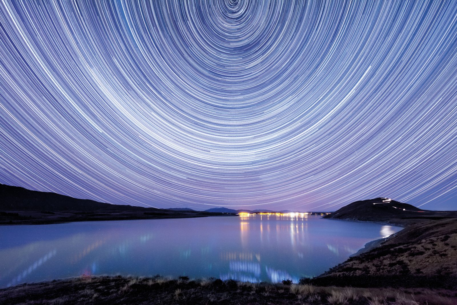 Stars appear to wheel above Lake Tekapo, recorded as concentric circles in this image—actually the result of 70 exposures of five minutes each, compiled together. In reality, however, it's the Earth that turns about the celestial south pole. Up on Mount John (to the right of the Tekapo lights), astronomers train lenses that automatically track across the sky to compensate for this spin.