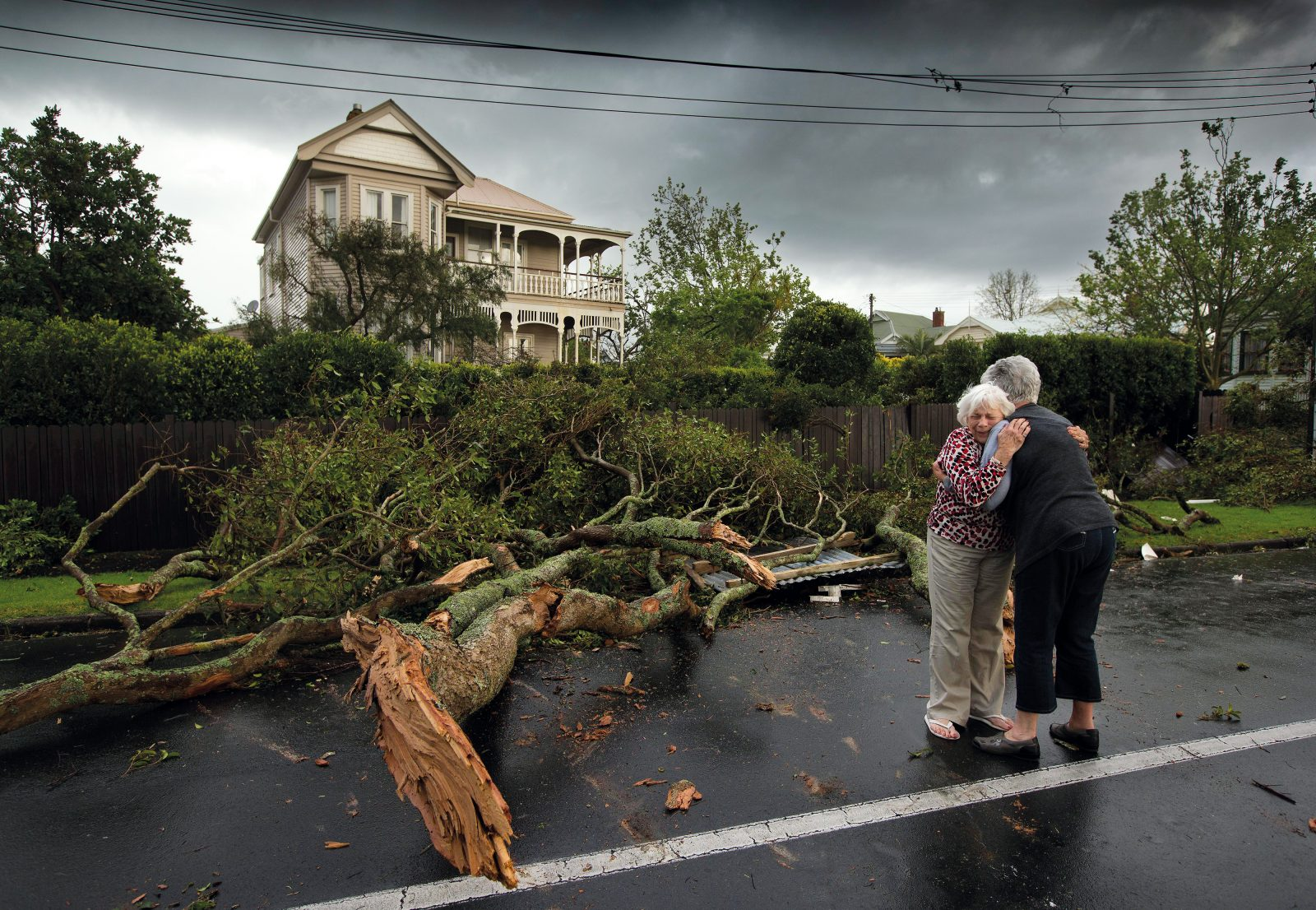 Devonport resident Shirley Wilma is comforted by a friend after a tornado ripped through the Auckland suburb on the evening of October 8, 2013. Brett Phibbs arrived on the scene shortly after the wind gusts struck and photographed the embrace of friends among uprooted trees and fallen power lines. A photographer for the New Zealand Herald, he says the most important thing in covering natural disasters is arriving quickly enough to capture the human reaction.