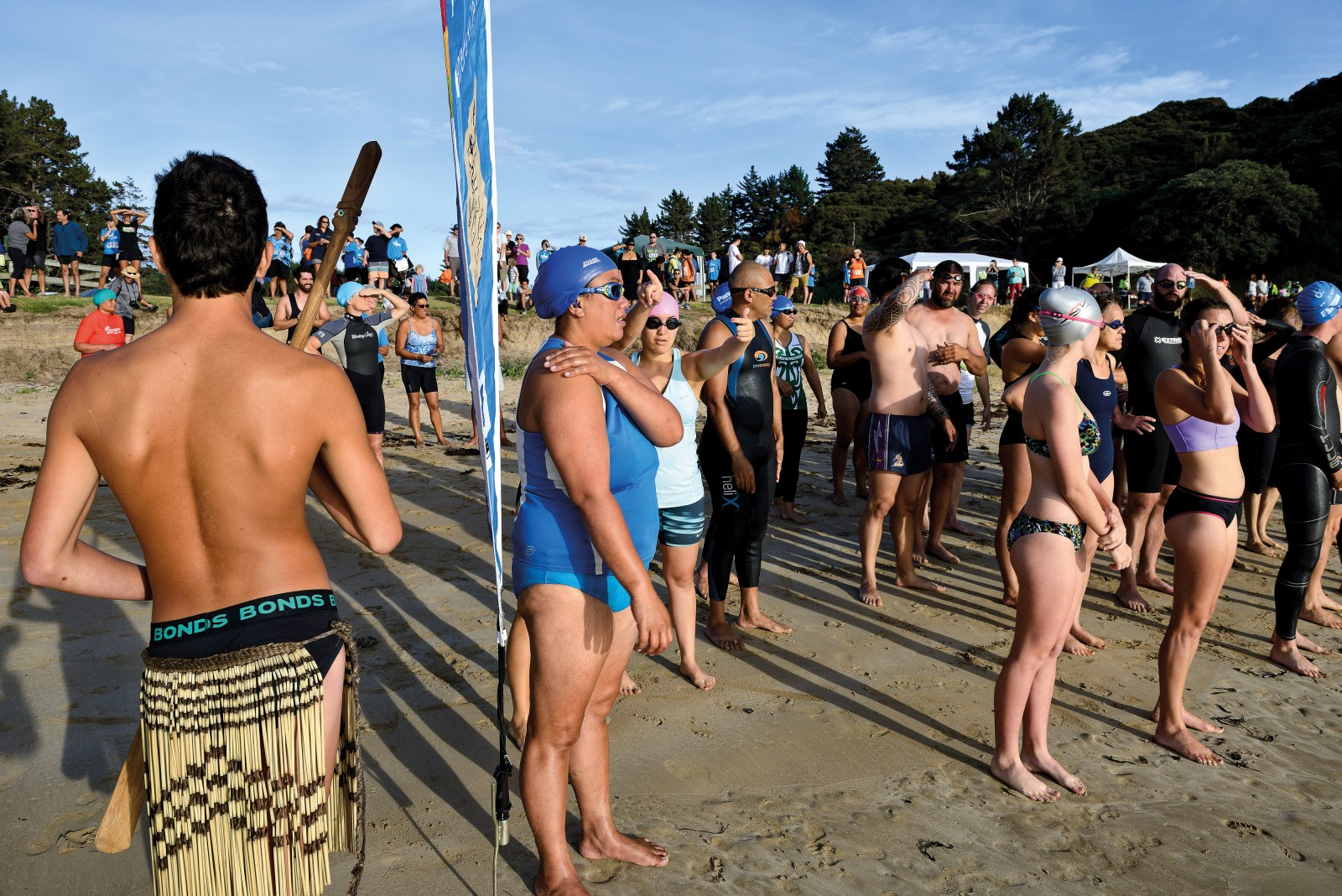 Multisport has come to Whangaroa in the form of the Iron Mahue, a one-kilometre ocean swim followed by a 10-kilometre run (or walk, for those who prefer a slower pace). The event's name comes from local hapū Ngāti Ruamahue, and the emphasis is less on breaking records than building community spirit and promoting a healthy lifestyle. Donald Morgan (back to camera) opened proceedings with a traditional challenge, and will stand guard on the beach until the last swimmer comes out of the water.