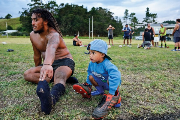 "Matiu Kahle stretches after rugby training, accompanied by his two-year-old son. ""Cassidy comes to every training and every game,"" says coach Kohai Kingi. ""He's our mascot."""