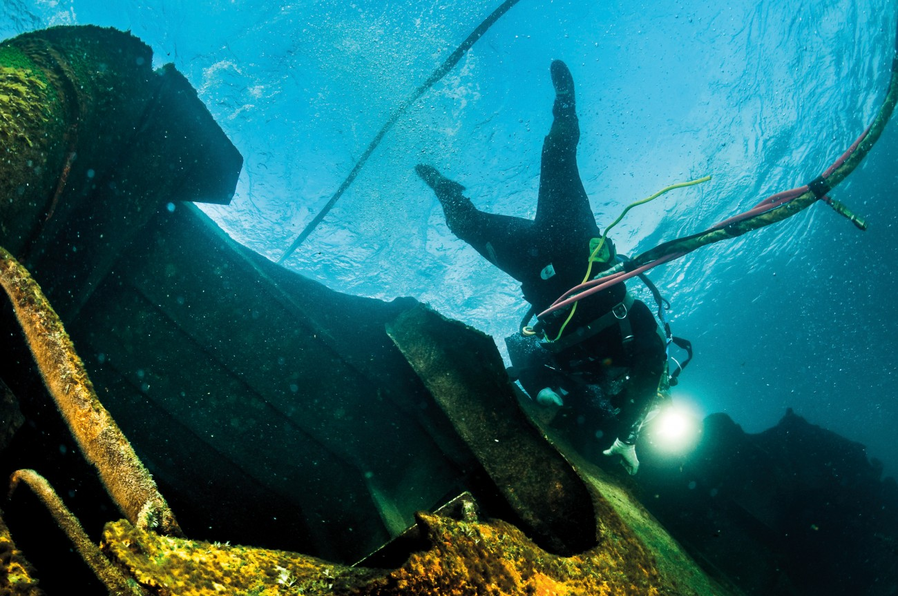 A commercial diver, with the umbilical hose that supplies air and allows communication, works on the bow section of the Rena, on top of the reef.