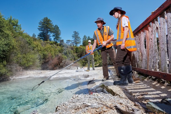 Researchers need to take a water sample—as Matthew Stott demonstrates to University of Waikato masters student Caitlin Lowe at a Whakarewarewa spring in Rotorua. Tests can then reveal the water's chemical and physical makeup—and the DNA of all the unseen life that lives in it.