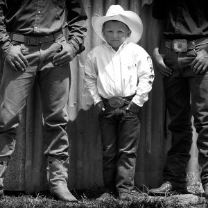 """Five-year-old Will Potts hangs out with a couple of cowboys at the Huntly Rodeo. Showjumper and New Zealand Herald photographer Christine Cornege was at the rodeo to shoot the bull riders and broncos, but during a lull in the action she wandered around looking for faces to photograph instead. She came across this boy chatting away to the men next to him. """"He thought he was about six feet tall,"""" she says. There are 35 rodeo clubs located around New Zealand, with more than 800 registered competitors."""