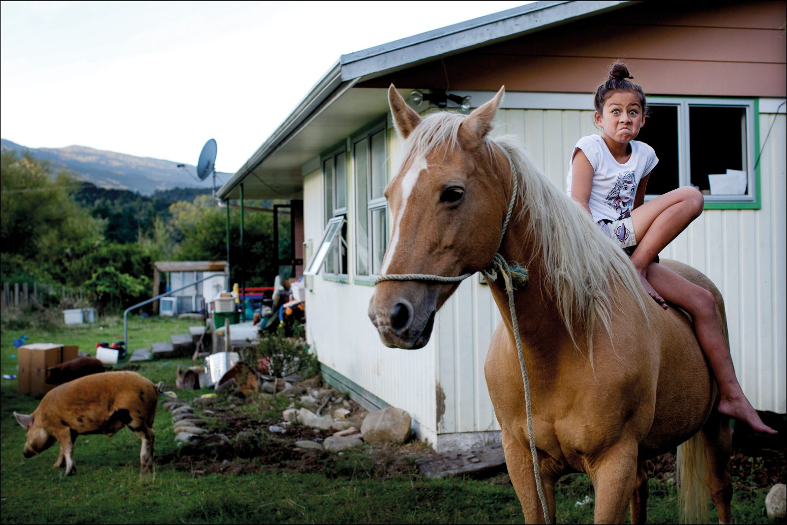 "Photographer David White travelled to the Urewera for a Sunday Star Times photo essay on the historic Treaty settlement with Tūhoe. ""The backbone of the story was going to hinge on an interview with tribal elder Tame Iti, but from a photographic point of view, I wanted to concentrate more on the Tūhoe youth,"" he says. In the village of Tuai, he came across nine-year-old Te Ataahia Lambert and her family; after a cup of tea, he asked if he could photograph the children while they tended their horses in the fading light. When he raised his camera to photograph Te Ataahia, she widened her eyes and clenched her mouth in a pūkana, a facial expression used for emphasis."