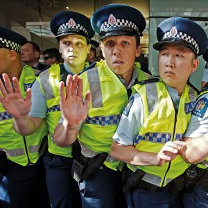 "Fairfax photojournalist Lawrence Smith was on the front line when protestors from Auckland Action Against Poverty rushed the police barricade at Sky City, where John Key was announcing sweeping budget changes. ""It was starting to get a little bit rowdy, when all of a sudden they charged the hotel entrance,"" says Smith. The police were taken by surprise, he says. Looking through his photographs from the day later, he was caught by the police officers' expressions of apprehension."