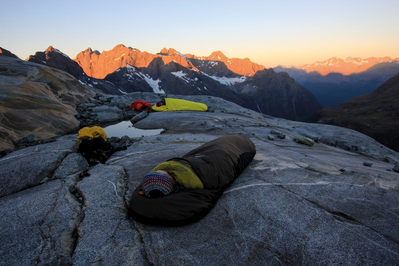 Finding a rock ledge flat enough to sleep on so high up a mountain is a godsend for climbers, especially at the end of a long day's climbing. At their feet is the mesmerising view over Moraine Creek and the Hollyford Valley.