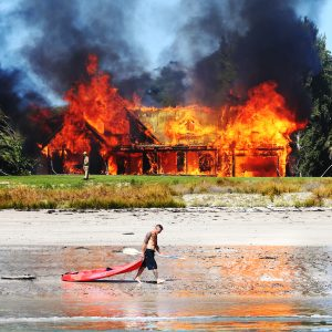 A multi-million dollar beachside mansion is torched as part of a training exercise for the Fire Service. New Zealand Herald photographer Doug Sherring observed the scene from a small boat moored in the bay, waiting for the decisive moment—when an oblivious kayaker crossed the scene.
