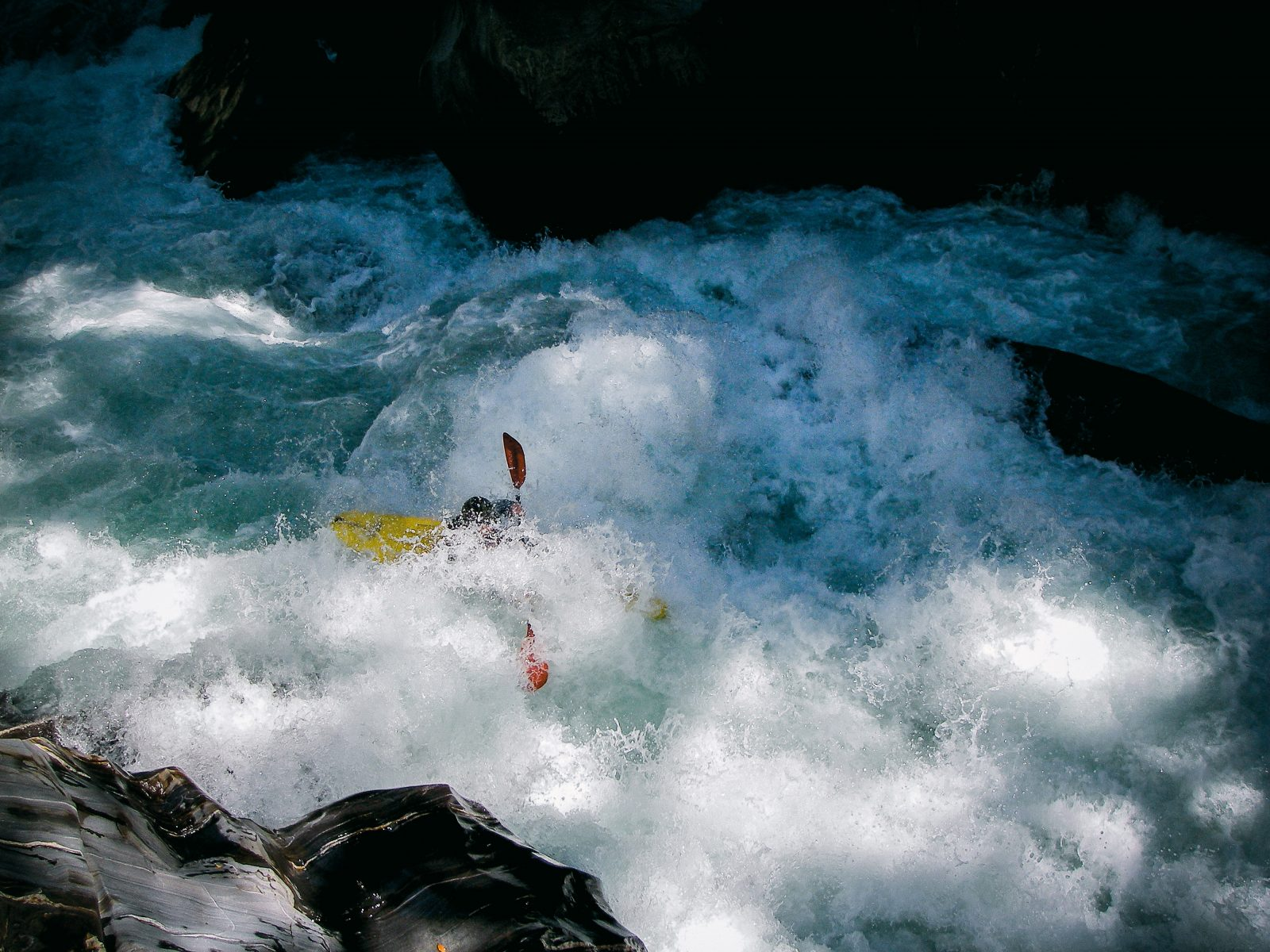 "Hidden in a froth of whitewater, Jason Shepherd takes on a rapid in the lower section of Morgan Gorge in 2008. Although parts of the gorge had been paddled since 2002, it was not until 2010 that a successful full descent was achieved. The gorge's swift flow and obstacle course of rock bluffs make the run one of the hardest in the country, navigible only by experts. Whitewater New Zealand, which represents the country's freshwater kayakers and opposes the hydro scheme, claims, ""There is no other resource offering the same mix and level of extremely challenging white water that can substitute for the Waitaha River."""