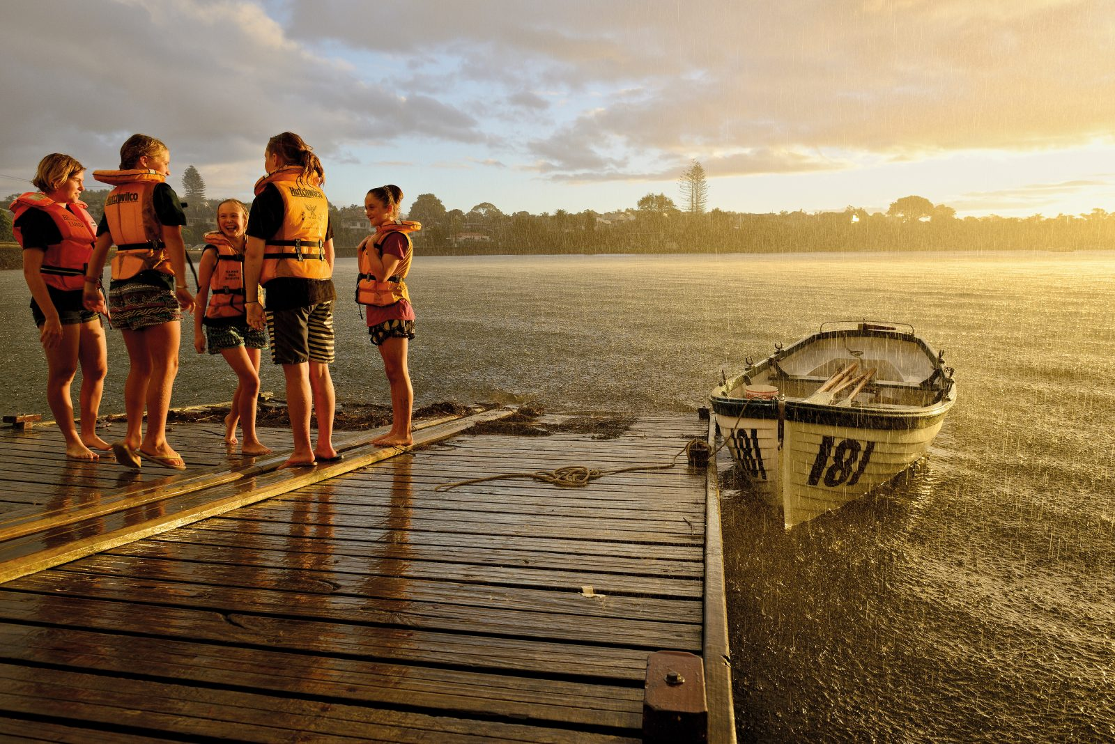 For more than a century, Auckland children have learned nautical skills at Cox's Bay, where the Hawke Sea Scouts have their clubhouse. Water conditions in the often-polluted bay determine which activities can be held safely. On a club night in late summer, a sudden downpour cut short the group's rowing practice, and the evening's water activity turned into dancing in the rain.